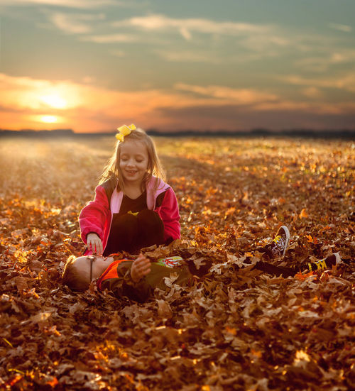 Portrait of smiling girl on field during autumn