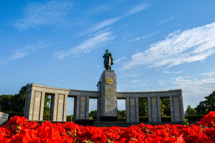 Red flowers in foreground, russian soldier monument in the background. Architecture Beauty In Nature Building Exterior Built Structure Cloud - Sky Day Flower Low Angle View Nature No People Outdoors Sky Statue Tree