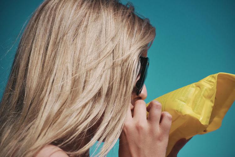 Woman blowing plastic against sky