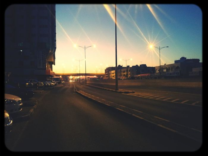 Road passing through city at sunset