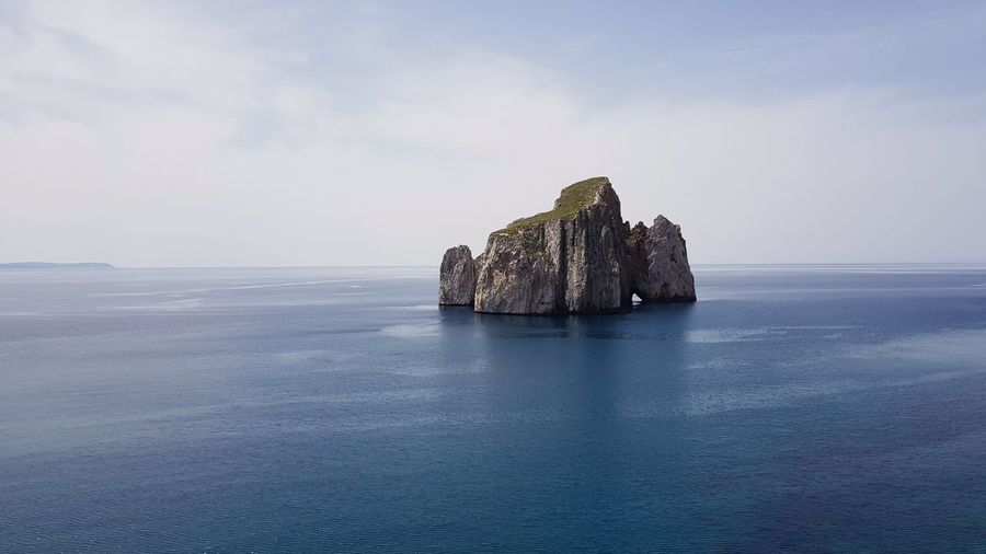 Scenic view of rock formation in sea against sky