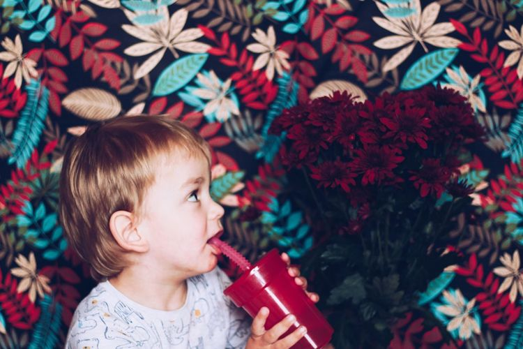 Close-up of cute girl drinking juice while looking at flowers