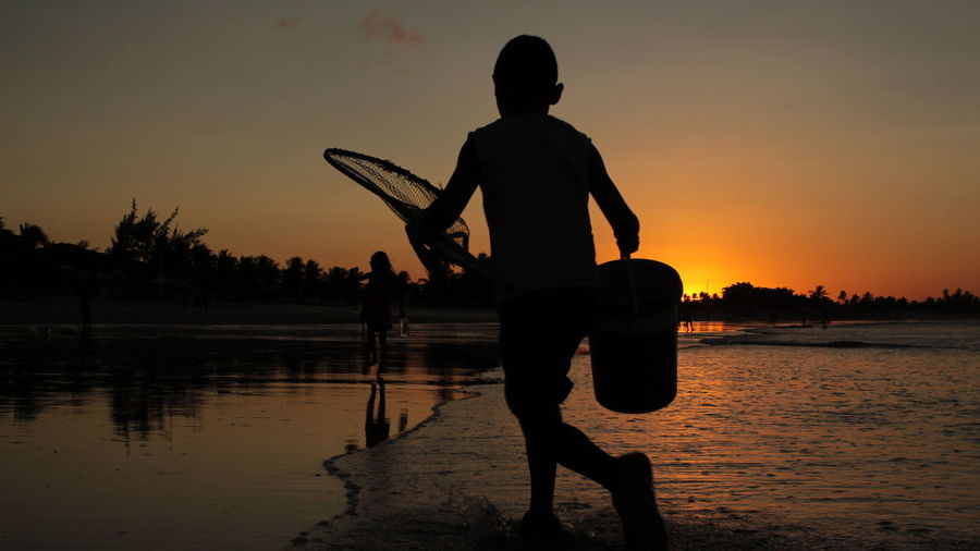 Silhouette boy with bucket and fishing net walking at beach during sunset