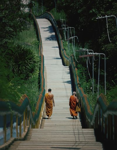 Rear view of monks walking on footbridge