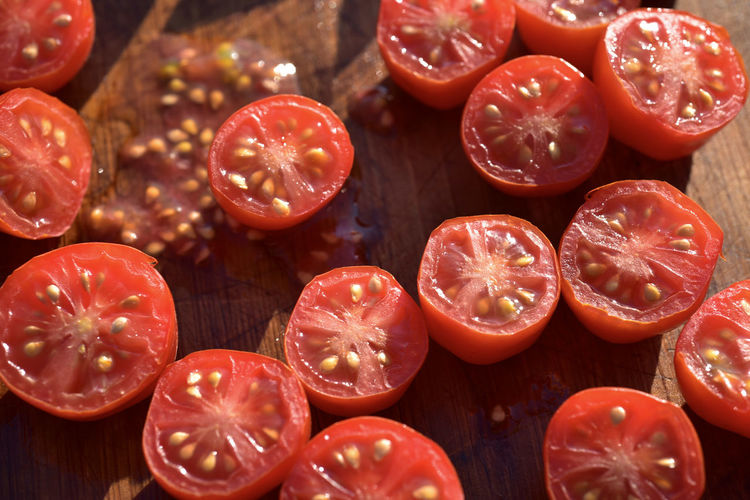 Above view of red grape tomatoes cut into halves on wood cutting board