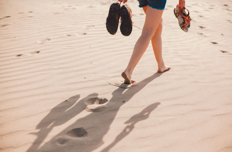 Low section of woman holding shoes while walking on sand at beach