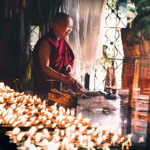 A monk lighting diyas for evening prayers.