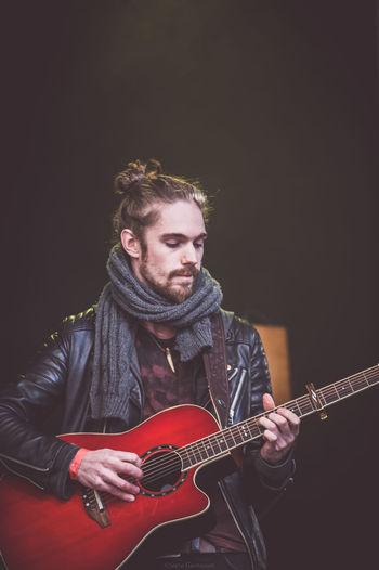 Fashionable musician playing guitar