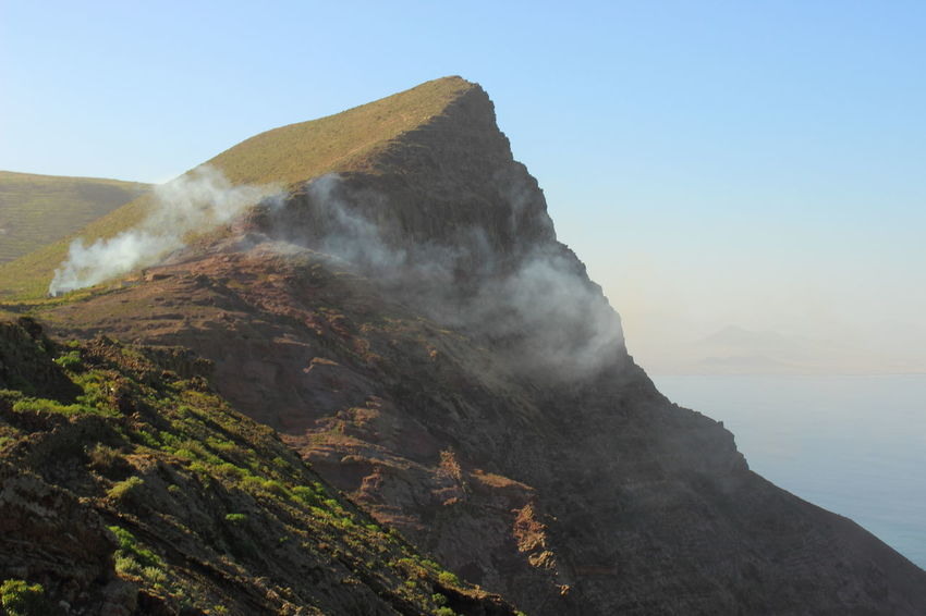 Canary Islands Lanzarote SPAIN Smoke Beauty In Nature Bush Fire Clear Sky Day Geology Landscape Mountain Mountain Range Nature No People Non-urban Scene Outdoors Rock - Object Sky Smoke Over Forest Tranquil Scene Tranquility Travel Destinations Volcanic Landscape Water The Traveler - 2018 EyeEm Awards The Great Outdoors - 2018 EyeEm Awards