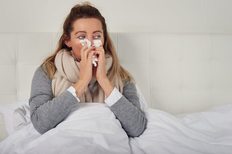 Sick woman with seasonal cold and flu Allergy Bed Copy Space Winter Woman Bed Bedroom Best Ager Blond Cold Flu Home Interior Ill Looking At Camera Middle-aged One Person Paper Tissue Real People Seasonal Sick Sickness Sneezing