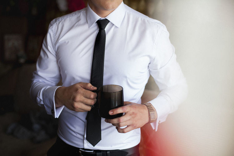 Midsection of businessman having coffee at home