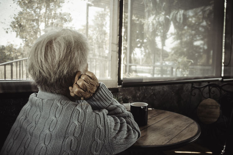 Rear view of old person sitting by window at home. concept loneliness, dementia, abuse, sadness.