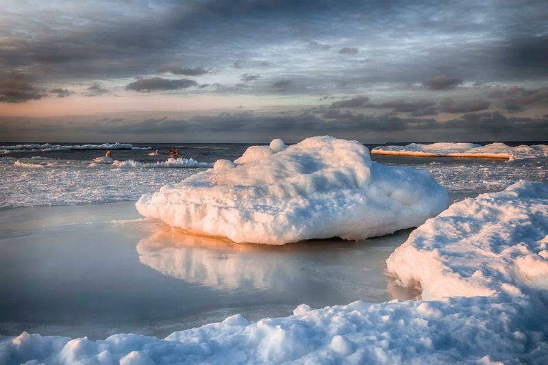 Scenic View Of Frozen Sea Against Cloudy Sky During Sunset