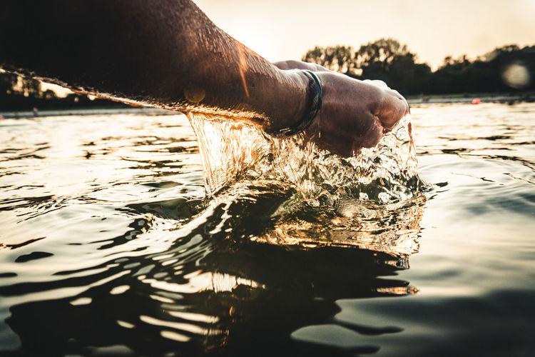 Cropped hands of man splashing water during sunset