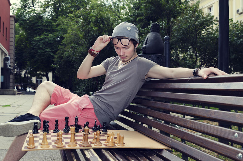Young handsome man playing chess in a city park Bench City European  Glasses Hat Sofia, Bulgaria Thinking Accessories Black Casual Clothing Caucasian Chess Chess Board Chess Piece Eyeglasses  Frame Game Handsome Leisure Activity Lifestyles One Person Outdoors Park Playing Summer