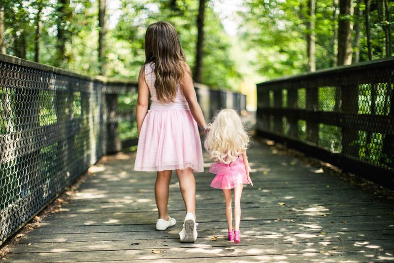 Rear View Of Girl With Dolls Walking On Footbridge In Forest