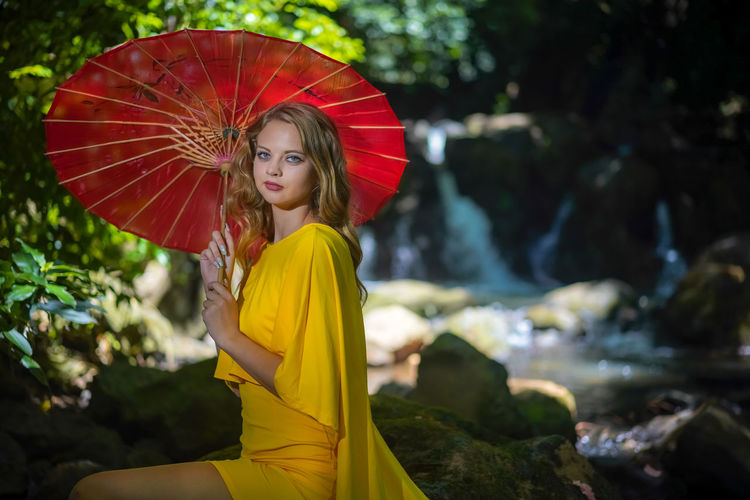 Portrait of a beautiful young woman with yellow umbrella