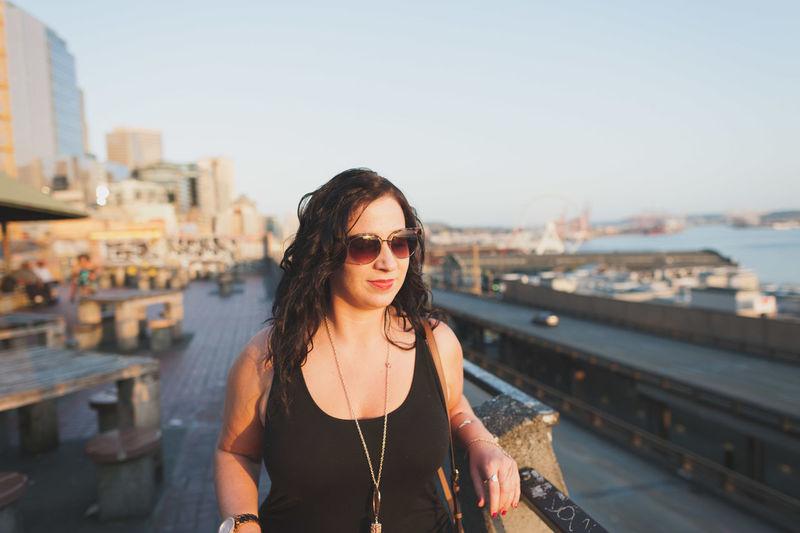 Beautiful woman standing by railing on walkway against sky