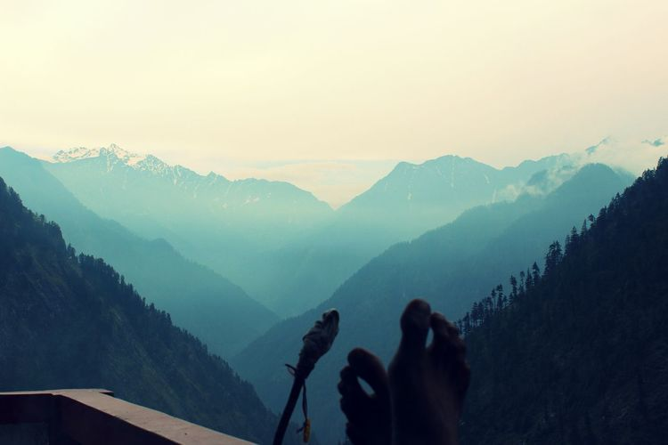 Low section of woman photographing mountains against clear sky