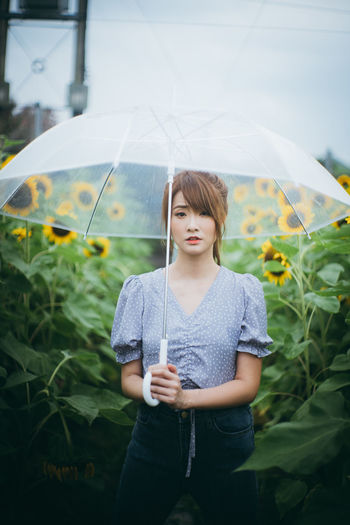Young woman looking down while standing against plants