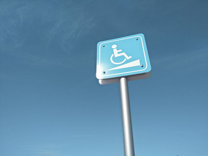Low angle view of disabled sign against blue sky