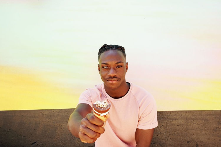Portrait of young man holding ice cream at beach against sky