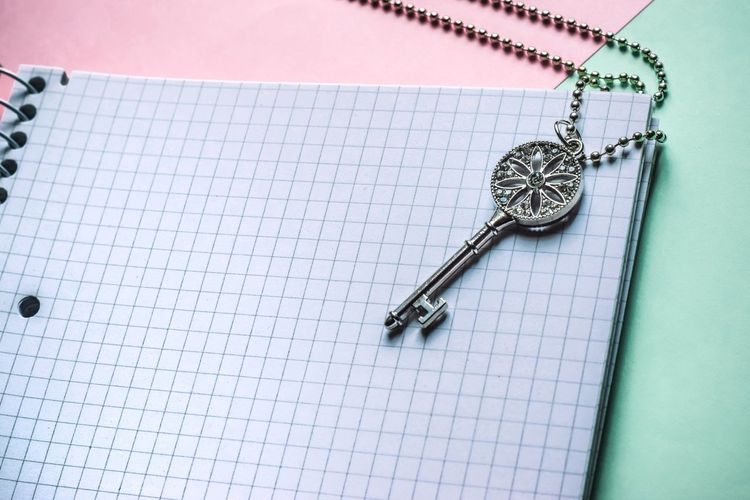 High angle view of key locket on spiral notebook on table