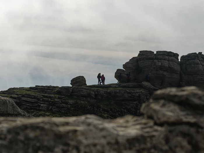 Low angle view of people on rocks against sky