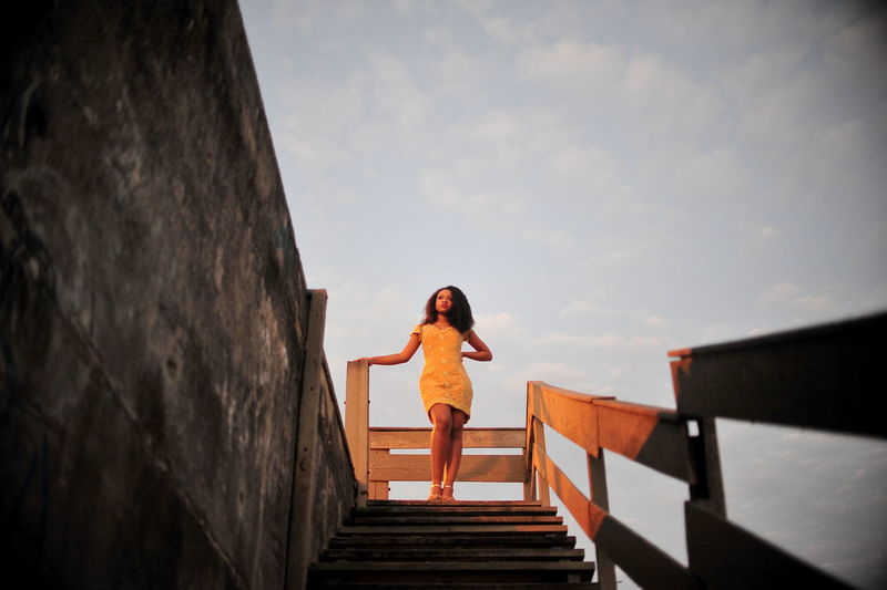Woman standing on staircase against sky