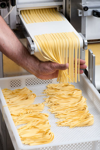 Cropped hand of man preparing spaghetti in factory
