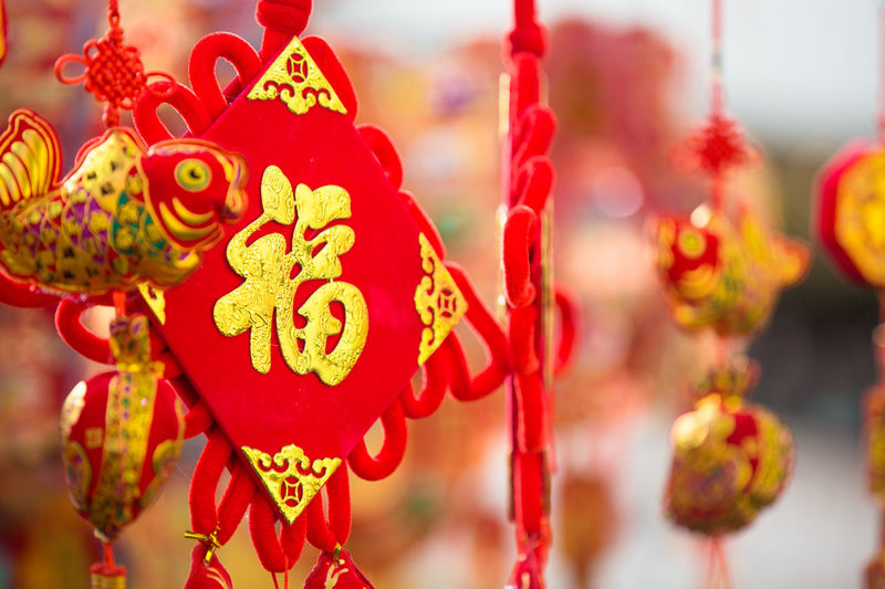 Close-Up Of Red And Gold Decorations Hanging At Market During Chinese New Year