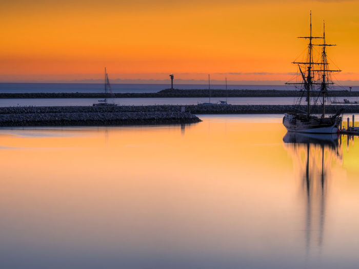 Golden Hour Mast Moored Boat At Sunset Moored Sailboat At Sunset No People Ocean Ocean Sunset  Orange Color Sailboat Sunset Tranquil Scene Tranquility Water
