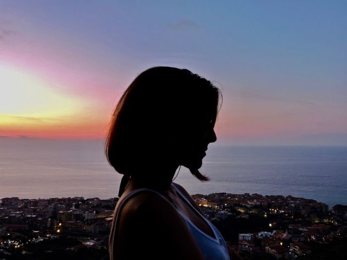 Side view of woman standing against sea during sunset