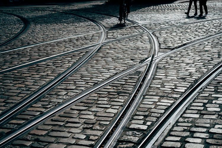 High angle view of railroad tracks on cobbled street in city