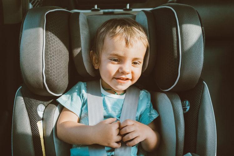 Cute baby boy sitting in car safety seat