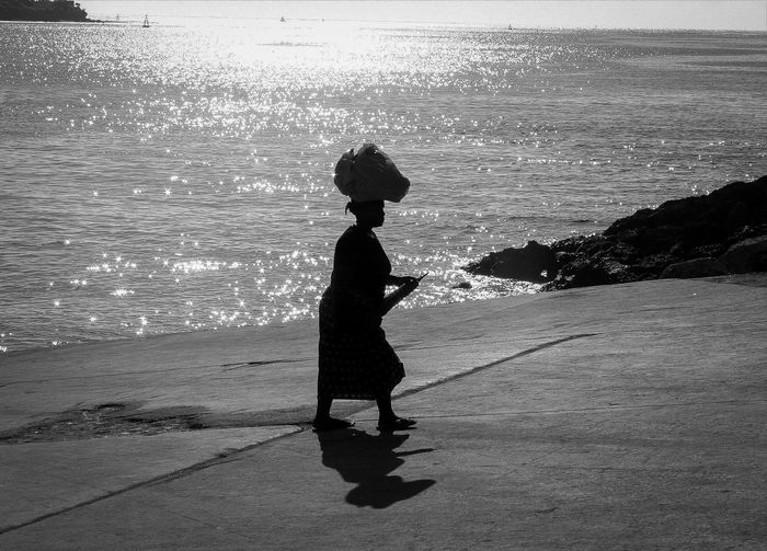 Woman in Mombasa Back Light Monochrome People Person Sea Silhouette Walking Water Woman Womans Work Working Travel Traveling Travel Photography Africa The Street Photographer - 2016 EyeEm Awards