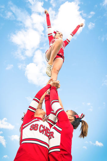 Low angle view of cheerleaders forming pyramid against cloudy sky