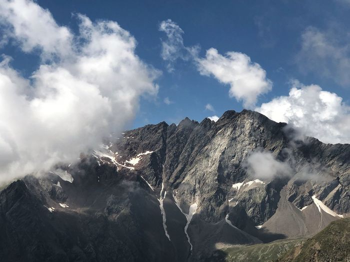 Panoramic view of snowcapped mountains against sky with clouds