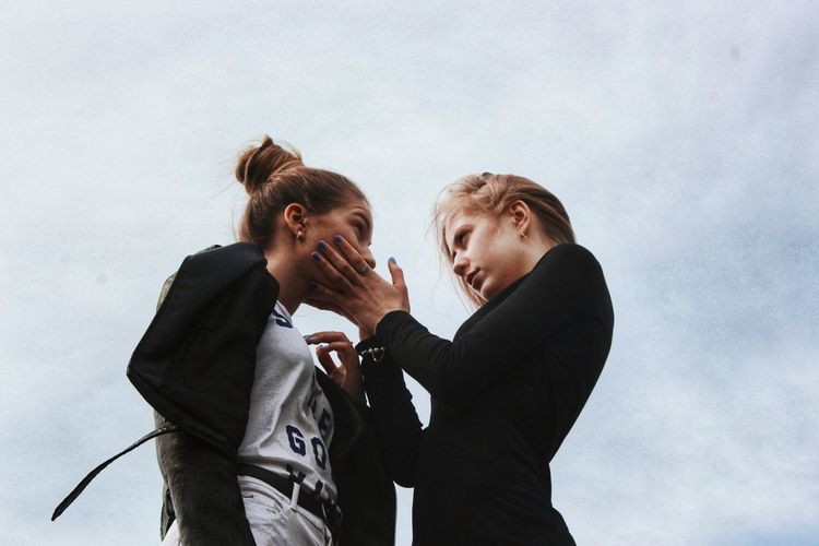Low angle view of lesbian couple standing against sky