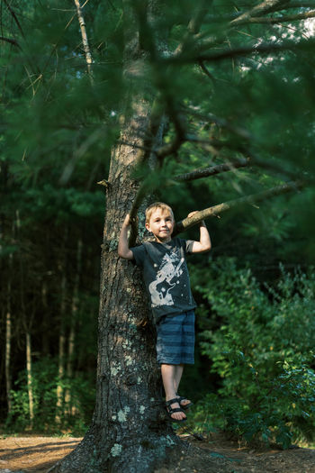 Full length portrait of happy girl standing on tree trunk in forest
