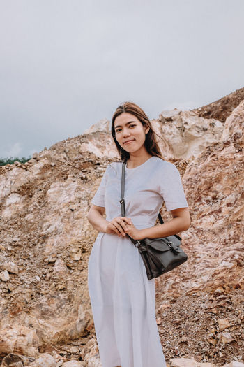 Adult Beautiful Woman Day Front View Hair Hairstyle Leisure Activity Lifestyles Looking At Camera Mountain Nature One Person Outdoors Portrait Real People Rock Sky Smiling Standing Three Quarter Length Women Young Adult Young Women