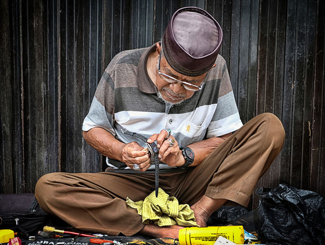 A street watch-repairman ... Old Man Sitting Streetphotography Street Life Small Business Trying To Make A Living Daily Life Handle With Care