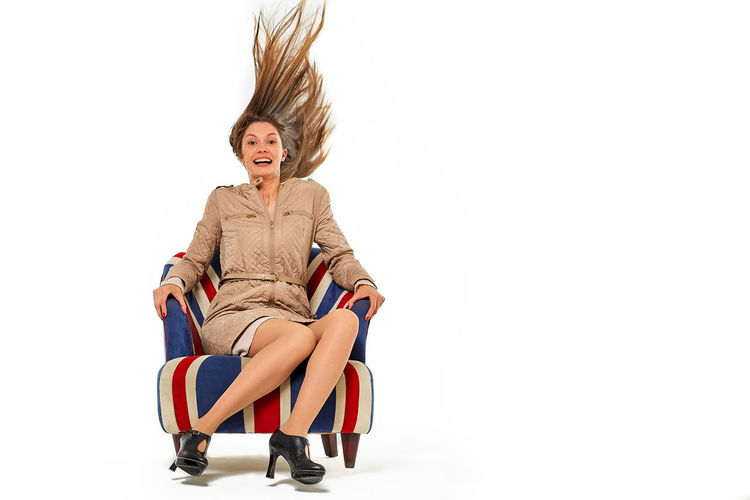 Woman sitting on chair against white background