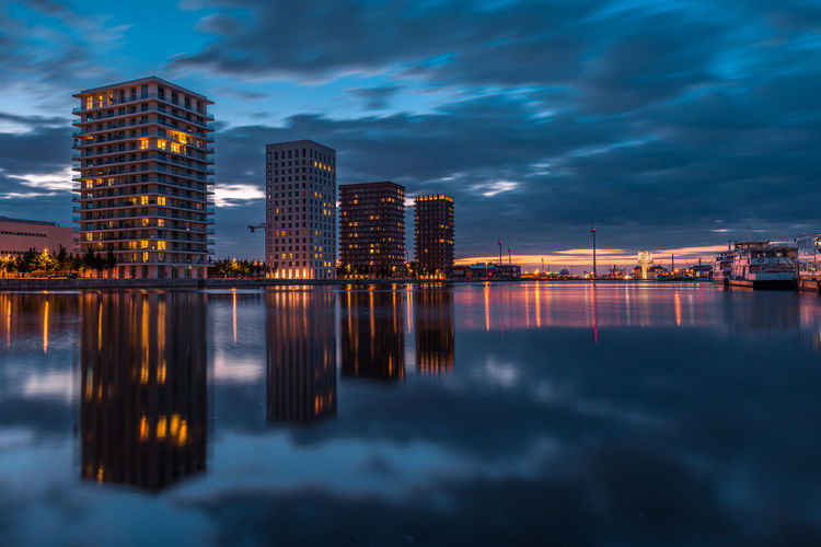 Reflection of illuminated buildings in city at sunset