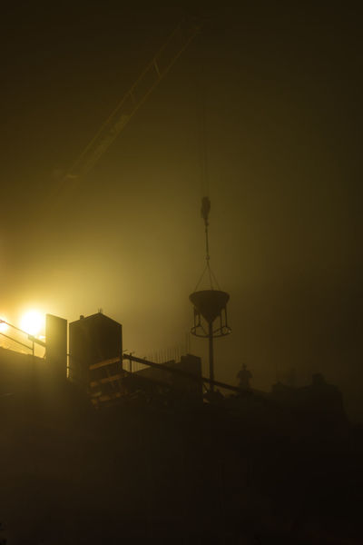 crane at a foggy evening in the city Architecture City Cityscape Construction Hopper Industry Work Worker Architecture Building Built Structure Crane darkness and light Fog Illuminated Job Jobsite  Lamp Low Angle View Mist Outdoors Overtime Project Silhouette Site