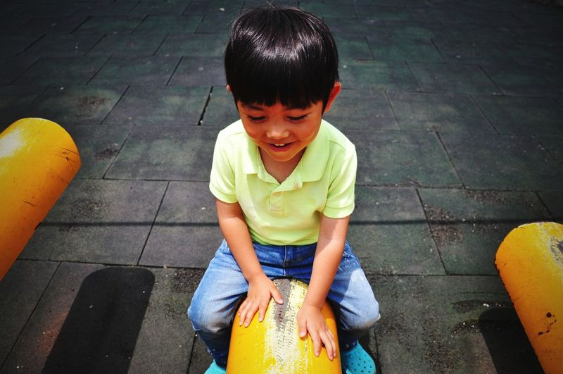 High Angle View Of Smiling Boy Sitting On Outdoor Play Equipment At Playground