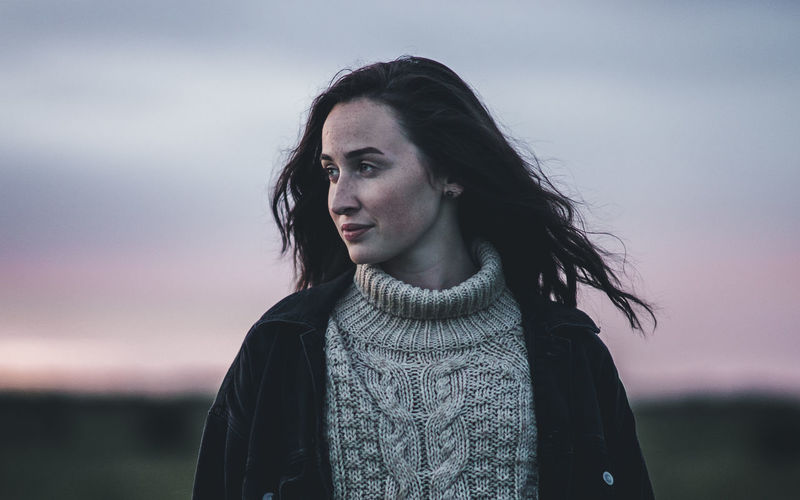 Young woman against sky