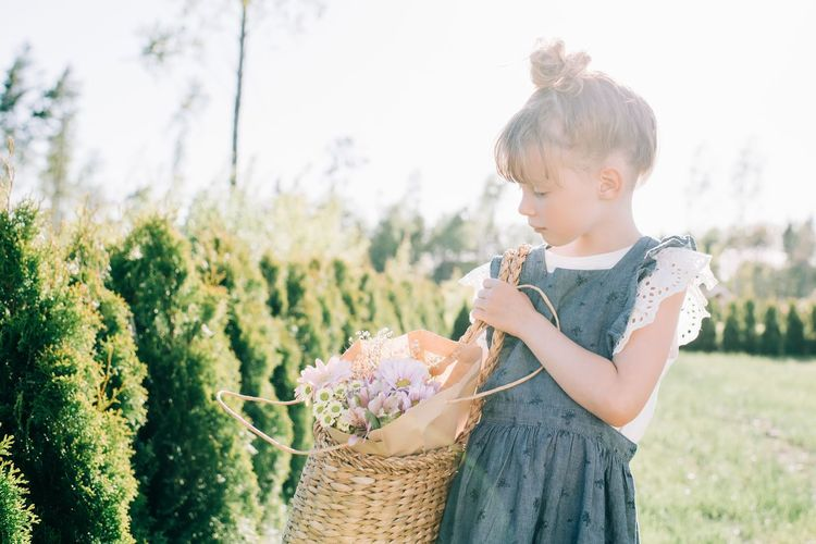 Cute girl holding basket while standing on field