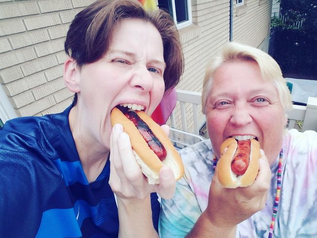 Eating Hot Dog Food Outside Lgbt Lesbian Couples Relationship Marriage  Female Family Backyard Casual Fun Funny Self Portrait Eating Human Hand Togetherness Portrait Fast Food Women Domestic Life Family Bonds