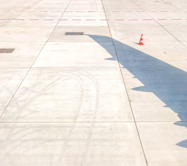 High angle view of aircraft wing shadow on runway